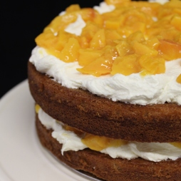 White velvet cake with white cloud frosting and layered with Southern Gold peach compote