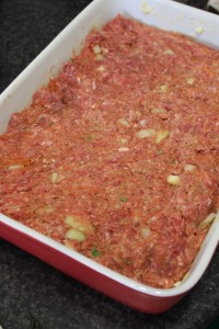 Butte a loaf or rectangle baking dish with butter, pat down meat mixture evenly.